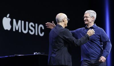 "In this June 8, 2015 file photo, Apple CEO Tim Cook, right, hugs Beats by Dre co-founder and Apple employee Jimmy Iovine at the Apple Worldwide Developers Conference in San Francisco when Apple announced Apple Music, an app that combines a 24-hour, seven-day live radio station called ""Beats"" with an on-demand music streaming service. (AP Photo/Jeff Chiu, File)"
