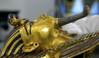 German restorer Christian Eckmann examines the beard of the famed golden mask of King Tutankhamun as an Egyptian-German team begins restoration work over a year after the beard was accidentally broken off and hastily glued back with epoxy, at the Egyptian Museum in Cairo, Egypt, Tuesday, Oct. 20, 2015. The 3,300-year-old burial pharaonic mask was discovered in Tutankhamun's tomb along with other artifacts by British archeologists in 1922, sparking worldwide interest in archaeology and ancient Egypt. (AP Photo/Amr Nabil)