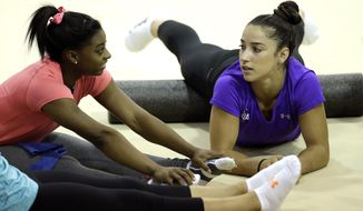 FILE - In this Sept. 12, 2015, file photo, U.S. gymnasts Aly Raisman, right, and Simone Biles stretch before a training session at the Karolyi Ranch in New Waverly, Texas. Stardom, the kind that truly changes a life, awaits Biles. The two-time defending world all-around champion will go for a three-peat at the 2015 championships in Glasgow, Scotland starting this weekend. (AP Photo/David J. Phillip, File)