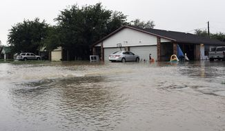 Water flows into a neighborhood Thursday, Oct. 22, 2015, in Midland County, Texas following heavy rains overnight. One home owner said he had water in his garage and his neighbor had water in his house. (Mark Sterkel/Odessa American via AP)