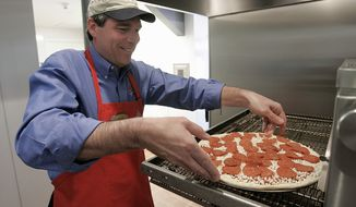 Domino's Pizza Chairman and Chief Executive Officer David A. Brandon is shown at company headquarters making a pizza in Ann Arbor, Mich., June 28, 2005. Now delivering pizza in 55 countries, Domino's Pizza Inc. is aggressively expanding its presence across the globe while at the same time adding access to domestic pizza eaters who are out of the current delivery area.   (AP Photo/Paul Sancya/File)