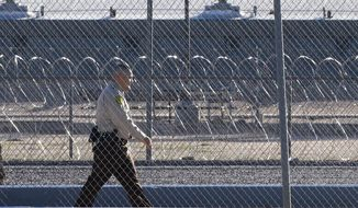 A corrections officer walks along a fence outside the Arizona Sate Prison in Florence, Ariz. (Associated Press)