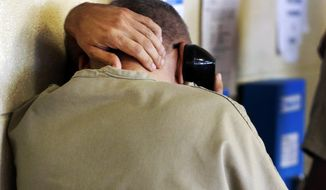 An inmate uses a phone at the Cook County Jail in Chicago, in this June 26, 2014, file photo. The Federal Communications Commission agreed on Thursday, Oct. 22, 2015, to slash rates on the vast majority of inmate's domestic and international calls to no more than $1.65 for 15 minutes. Fees and other costs, which in some cases have boosted calls to $17 to $25 for 15 minutes, also would be limited. (AP Photo/Charles Rex Arbogast, File)