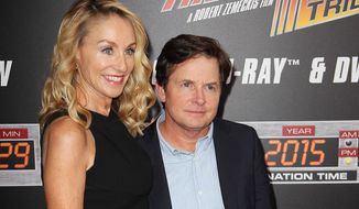 "In this image released by Starpix, Michael J. Fox, right, and his wife Tracy Pollan arrive at the ""Back To The Future"" 30th Anniversary celebration, Wednesday, Oct. 21, 2015, in New York. Fox portrayed Marty McFly and Seamus McFly in the trilogy. (Matthew Taplinger/Starpix via AP) ** FILE **"