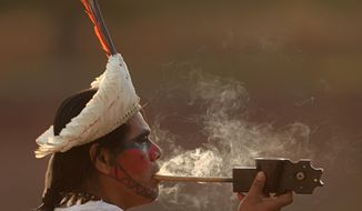 Tobi Itauna, of the Tupi Guarani ethnic group, smokes his traditional pipe in the arena of World Indigenous Games in Palmas, Brazil, Wednesday, Oct. 21, 2015. Palmas is the host city for the first World Indigenous Games that will showcase traditional sports with the participation of more than 2,000 indigenous athletes from around the world. The event begins Oct. 23 and runs through Nov. 1. (AP Photo/Eraldo Peres)