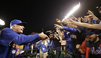 New York Mets manager Terry Collins sprays some fans after Game 4 of the National League baseball championship series against the Chicago Cubs Wednesday, Oct. 21, 2015, in Chicago. The Mets won 8-3 to advance to the World Series. (AP Photo/David Goldman)