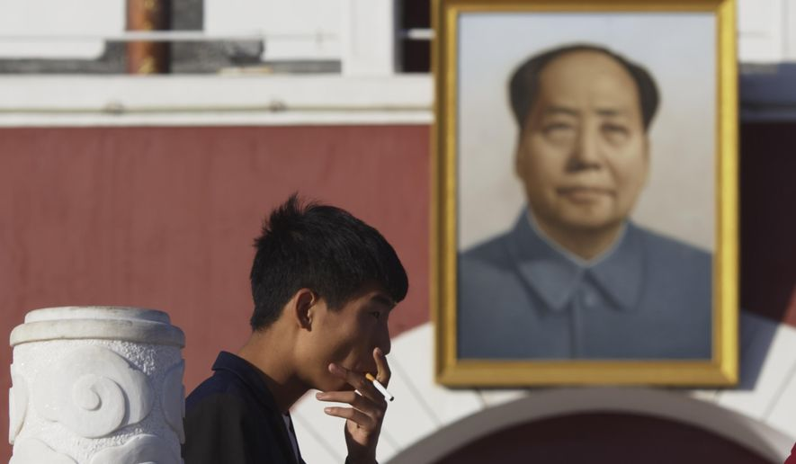 A man smokes near a portrait of late Chinese leader Mao Zedong hung on a replica of the Tiananmen Gate in Yinchuan in northwestern China's Ningxia Hui autonomous region on Thursday, Oct. 8, 2015.  Research published in the medical journal The Lancet says one in three of all the young men in China are likely to die from tobacco, but that the number can fall if the men quit smoking. (AP Photo/Ng Han Guan)