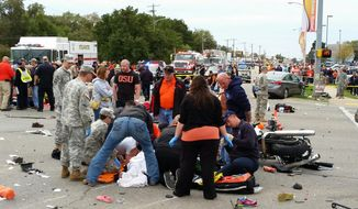 Emergency personnel and spectators respond after a vehicle crashed into a crowd of spectators during the Oklahoma State University homecoming parade, causing multiple injuries, on Saturday, Oct. 24, 2015 in Stillwater, Oka.  (David Bitton/The News Press via AP) MANDATORY CREDIT