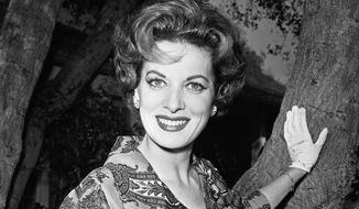 This Jan. 19, 1960, file photo shows movie actress Maureen O'Hara photographed in her front yard in Los Angeles. (AP Photo/Harold Filan, File)