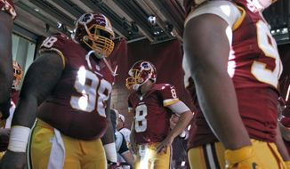 Washington Redskins quarterback Kirk Cousins (8) waits with defensive tackle Terrance Knighton (98) nearby, to enter the field before an NFL football game against the Miami Dolphins, Sunday, Sept. 13, 2015, in Landover, Md. (AP Photo/Alex Brandon)