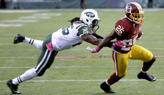 Washington Redskins quarterback Robert Griffin III, bottom right, reacts as teammate Chris Thompson is treated on the sideline during an injury in the first half of an NFL football game against the New York Jets, Sunday, Oct. 18, 2015, in East Rutherford, N.J. (AP Photo/Gary Hershorn)