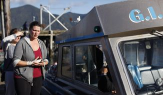 Jenn Newman, one of the survivors rescued after the Leviathan II sank, visits First St. dock and the G.I. Charles boat that rescued her, before leaving Tofino, British Columbia, Monday, Oct. 26, 2015. The whale watching boat with over two dozen people on board sank Sunday off Vancouver Island, the British Foreign Minister said Monday, killing multiple people. (Chad Hipolito/The Canadian Press via AP)