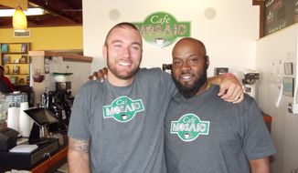 In this Oct. 14, 2015 photo, former Benton Harbor Police Officer Andrew Collins, left, and the man he put in prison, Jameel McGee, pose for a photo at Cafe Mosaic in Benton Harbor, Mich. Mr. Collins served 18 months in prison for his crimes and is now the cafe's manager, where he recently started mentoring Mr. McGee. The two want to share their story of redemption and forgiveness with others. (Louise Wrege/The Herald-Palladium via AP)