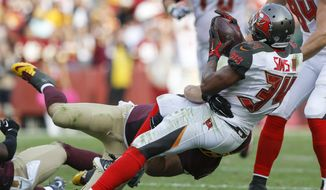 Tampa Bay Buccaneers running back Charles Sims (34) fumbles the ball on a hit by Washington Redskins inside linebacker Will Compton (51) during the second half of an NFL football game in Landover, Md., Sunday, Oct. 25, 2015. The Washington Redskins defeated the Tampa Bay Buccaneers 31-30. (AP Photo/Patrick Semansky)
