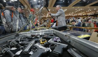 Handguns are displayed at the table of gun store owner David Petronis of Mechanicville, N.Y. as he holds a rifle during the annual New York State Arms Collectors Association Albany Gun Show in Albany, N.Y. (Associated Press)