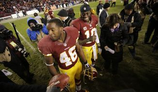 Washington Redskins quarterback Robert Griffin III,center, and teammate Alfred Morris wait to be interviewed after an NFL football game against the Dallas Cowboys on Sunday, Dec. 30, 2012, in Landover, Md. The Redskins won 28-18 to win the NFC East. (AP Photo/Evan Vucci)