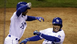 Kansas City Royals' Alcides Escobar celebrates after scoring the game-winning run during the 14th inning of Game 1 of the Major League Baseball World Series against the New York Mets Wednesday, Oct. 28, 2015, in Kansas City, Mo. The Royals won 5-4 to take a 1-0 lead in the series. (AP Photo/David Goldman)