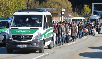 German federal police guide a group of migrants on their way after crossing the border between Austria and Germany in Wegscheid near Passau, Wednesday, Oct. 28, 2015. (AP Photo/Kerstin Joensson) ** FILE **