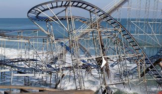 In this Nov. 29, 2012 photo, the Jet Star roller coaster is battered by the surf after it plunged into the ocean at Seaside Heights N.J. during Superstorm Sandy. Three years after the storm, most coastal tourism facilities in New Jersey and New York have been rebuilt.(AP Photo/Wayne Parry, File)
