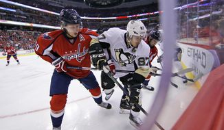 Washington Capitals center Nicklas Backstrom (19), from Sweden, and Pittsburgh Penguins center Sidney Crosby (87) battle for the puck in the first period of an NHL hockey game, Wednesday, Oct. 28, 2015, in Washington. (AP Photo/Alex Brandon)