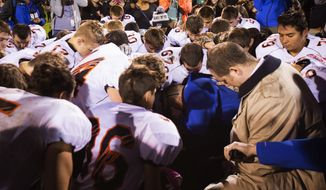 Bremerton (Wash.) High School assistant football coach Joe Kennedy (center) prays with his team despite orders to stop. Mr. Kennedy was subsequently placed on paid administrative leave. (Seattle Times via Associated Press)