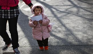 In this Monday, Feb. 28, 2011, file photo, a woman leads a child in Beijing Monday, Feb. 28, 2011.  China's ruling Communist Party announced Thursday, Oct. 29, 2015,  that it will abolish the country's decades-old one-child policy and allow all couples to have two children, removing remaining restrictions that limited many urban couples to only one, the official Xinhua News Agency said.  (AP Photo/Andy Wong, File)