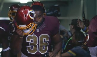 Washington Redskins fullback Darrel Young (36) puts on his helmet as he runs on to the field before an NFL football game against the Tampa Bay Buccaneers in Landover, Md., Sunday, Oct. 25, 2015. (AP Photo/Patrick Semansky)