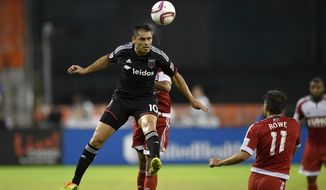 D.C. United forward Fabian Espindola (10) heads the ball against New England Revolution midfielder Kelyn Rowe (11) during the first half of an MLS playoff soccer game, Wednesday, Oct. 28, 2015, in Washington. (AP Photo/Nick Wass)