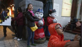 A woman gestures towards two dolls depicting children near a child in Beijing, China, Thursday, Oct. 29, 2015. The official Xinhua News Agency says China's ruling Communist Party has decided to abolish the country's one-child policy and allow all couples to have two children. (AP Photo/Ng Han Guan)