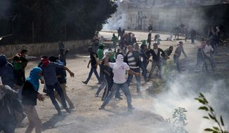 Palestinian students hurl stones at Israeli troops over the separation barrier during clashes following a protest near the Al-Quds University in the West Bank village of Abu Dis, near Jerusalem, Wednesday, Oct. 28, 2015. (AP Photo/Majdi Mohammed) ** FILE **