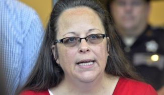 Rowan County Clerk Kim Davis makes a statement to the media at the front door of the Rowan County Judicial Center in Morehead, Ky., in this Sept. 14, 2015, file photo. For the first time, most Americans expect government officials to issue marriage licenses to same-sex couples, even over religious objections, an Associated Press-GfK poll has found. Last summer, Davis refused to issue marriage licenses to gay couples. (AP Photo/Timothy D. Easley, File)