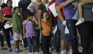 In this June 20, 2014, file photo, immigrants who entered the U.S. illegally stand in line for tickets at the bus station after they were released from a U.S. Customs and Border Protection processing facility in McAllen, Texas. (AP Photo/Eric Gay, File)