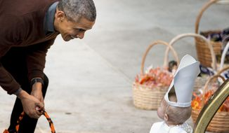 President Barack Obama greets a child dressed as the Pope during Halloween festivities at the South Portico of the White House in Washington, Friday, Oct. 30, 2015. The first couple welcomed local children and children of military families to 'trick-or-treat' at the White House for Halloween. (AP Photo/Andrew Harnik)
