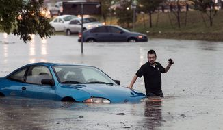 Mike Stoner gets out of his flooded car, Friday, Oct. 30, 2015, in San Marcos, Texas. A fast-moving storm packing heavy rain and destructive winds overwhelmed rivers and prompted evacuations Friday in the same area of Central Texas that saw devastating spring floods. (Rodolfo Gonzalez/Austin American-Statesman via AP)