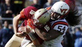 Virginia Tech linebacker Andrew Motuapuaka (54) sacks Boston College quarterback Troy Flutie (16) during the first quarter of an NCAA college football game in Boston, Saturday, Oct. 31, 2015. (AP Photo/Michael Dwyer)