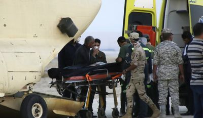 Egyptian emergency workers unload bodies of victims from the crash of a Russian aircraft carrying 217 passengers and 7 crew members over the Sinai peninsula from a police helicopter to ambulances at Kabrit airport in Suez, some 20 miles north of Suez, Egypt, Saturday, Oct. 31, 2015. (AP Photo/Amr Nabil)