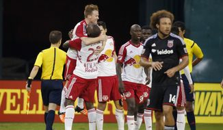 New York Red Bulls defender Ronald Zubar (23) picks up midfielder Dax McCarty (11) as D.C. United midfielder Nick DeLeon (14) walks off the field after an MLS playoff soccer match, at RFK Stadium, Sunday, Nov. 1, 2015, in Washington. New York won 1-0. (AP Photo/Alex Brandon)