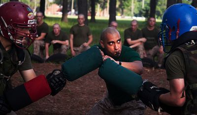 Sgt. Roberto Martinez, a martial arts instructor at Marine Corps Recruit Depot Parris Island, S.C., initiates a pugil stick match during training July 8, 2013. Each recruit participated in two matches. Recruits train with pugil sticks, which represent rifles with attached bayonets, to simulate close-range encounter with an enemy. Bayonet training, along with other hand-to-hand fighting skills, is encompassed in the Marine Corps Martial Arts Program, which contributes to the mental, character and physical development of Marines. Approximately 20,000 recruits come to Parris Island annually for the chance to become Marines by enduring 13 weeks of rigorous, transformative training. Parris Island is home to entry-level enlisted training for 50 percent of men and 100 percent of women in the Marine Corps. Martinez is from West Covina, Calif.  (U.S. Marine Corps photo by Lance Cpl. David Bessey)