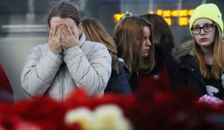 People react, at an entrance of Pulkovo airport during a day of national mourning for the victims of the plane crash, outside St. Petersburg, Russia, Tuesday, Nov. 3, 2015. (AP Photo/Dmitry Lovetsky)