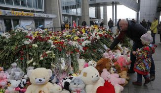 A man and his daughter put flowers and a toy at an entrance of Pulkovo airport outside St. Petersburg, Russia, Wednesday, Nov. 4, 2015. A Russian official says families have identified the bodies of 33 victims killed in Saturday's plane crash over Egypt. (AP Photo/Dmitry Lovetsky)