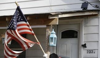 A tattered flag flies in front of a home where Julian Hernandez lived with his father, Bobby Hernandez, Thursday, Nov. 5, 2015, in Cleveland. Thirteen years after Julian was allegedly snatched from his Alabama home at age 5 by his father, the young man has been found living under an assumed name with his dad in Ohio, in a case authorities say broke open when his Social Security number raised red flags during college applications. (AP Photo/Tony Dejak)