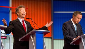 In this photo taken Aug. 6, 2015, Republican presidential candidate Sen. Rand Paul, R-Ky., left, accompanied by Ohio Gov. John Kasich, speaks during the first Republican presidential debate at the Quicken Loans Arena in Cleveland. (AP Photo/Andrew Harnik) ** FILE **
