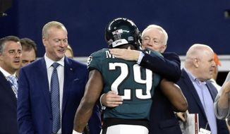 Jerry Jones Jr., second from left, watches as Philadelphia Eagles running back DeMarco Murray (29) receives a hug from Dallas Cowboys team owner Jerry Jones, right, during team warmups before an NFL football game Sunday, Nov. 8, 2015, in Arlington, Texas. (AP Photo/Michael Ainsworth)