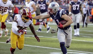 New England Patriots wide receiver Julian Edelman (11) gives a stiff arm to Washington Redskins defensive back Jeron Johnson (20) after catching a pass during the second half of an NFL football game Sunday, Nov. 8, 2015, in Foxborough, Mass. (AP Photo/Steven Senne)