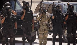 In this Thursday, June 20, 2013, file photo, special operations forces from Iraq, Jordan and the U.S. stand in formation wearing gas masks following a combined demonstration as part of Eager Lion multinational military maneuvers at the King Abdullah Special Operations Training Center (KASOTC) in Amman, Jordan. The government-owned Al-Rai newspaper says a Jordanian policeman opened fire on American contractors at a police training center, killing two and injuring three. (AP Photo/Maya Alleruzzo, File)