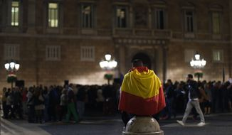 "A man wraps with a Spanish flag during a demonstration calling for the ""unity of Spain"" in Barcelona, Spain, Thursday, Nov. 5, 2015. (AP Photo/Manu Fernandez)"