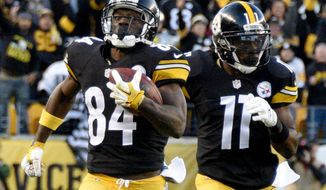 Pittsburgh Steelers wide receiver Antonio Brown (84) runs with Markus Wheaton ahead of Oakland Raiders defenders after making a catch to help set up the Steelers game winning field goal in the fourth quarter of an NFL football game against the Oakland Raiders, Sunday, Nov. 8, 2015, in Pittsburgh. (AP Photo/Don Wright)
