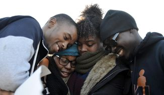 Members of Concerned Student 1950 embrace after the announcement that University of Missouri System President Tim Wolfe would resign Monday, Nov. 9, 2015, in Columbia, Mo. Wolfe resigned Monday with the football team and others on campus in open revolt over his handling of racial tensions at the school. (Halee Rock/Missourian via AP)