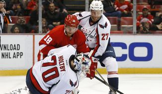 Washington Capitals goalie Braden Holtby (70) stops a Detroit Red Wings center Joakim Andersson (18) shot as defenseman Karl Alzner (27) defends in the second period of an NHL hockey game Tuesday, Nov. 10, 2015, in Detroit. (AP Photo/Paul Sancya)