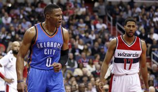 Oklahoma City Thunder guard Russell Westbrook (0) reacts after a dunk, near Washington Wizards guard Garrett Temple (17) during the second half of an NBA basketball game Tuesday, Nov. 10, 2015, in Washington. The Thunder won 125-101. (AP Photo/Alex Brandon)
